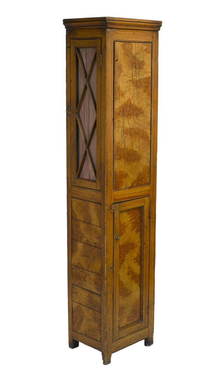 Tall cupboard square in plan, doors on two of four sides, each door opens on a cupboard with two shelves, upper has glass panels in lattice design and red cotton curtain, lower has wooden door, from Fala Dam.