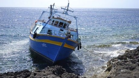 Can more be done to help people crossing the Mediterranean? A boat on the rocks off the Italian island of Lampedusa.
