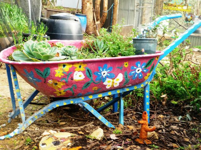 painted and planted wheelbarrow in the garden