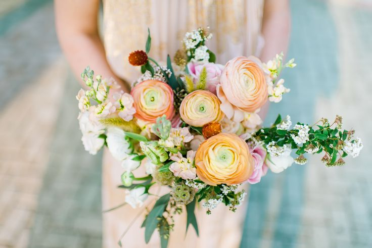 loose bridesmaid bouquet of white ranunculus, peach stock, rosita vendela roses, echinacea pods, white majolik spray roses, bunny tail grass, peach ranunculus, scabiosa pods, white parrot tulips, elm and seeded eucalyptus wrapped in cream satin ribbon.