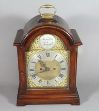 """Lot 194 - A Victorian mahogany bracket clock in the Georgian style, having a silvered chapter ring inscribed W & H Trimnell Canterbury, the domed case with brass carrying handle and on brass feet 18"""" x 11"""" x 6""""... £450-550"""