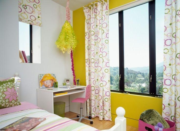 gelbe Akzentwand und rosa-grüne Dekorationen im Kinderzimmer