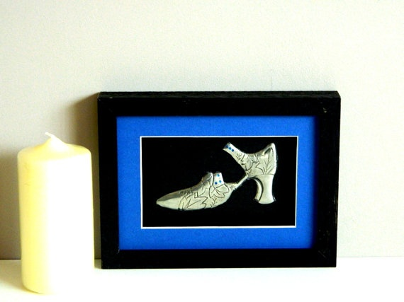 A metal art sculpture pewter embossed shoe trimmed with Capri Blue Swarovski crystals. A black frame and royal blue mount complete this framed metal sculpture.    Build a collage to make a lovely bedroom wall feature.