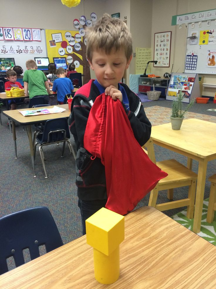 Don't peek! Kindergartners reach in to feel a 3D shape and describe its characteristics to the class. Does it have corners, edges, faces? How many? Can anyone guess the name of the shape before he shows it?