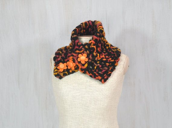 Chunky merino scarf, soft woolen scarf, brown black orange wool, textile flowers, neck warmer, soft, thick wool, OOAK  This chunky knit scarf is the perfect addition for cold days. It is made of pure wool in warm colors. Decorated with handmade textile buttons — orange flowers.  Width (without stretching): ca 7.5 (19 cm) Length: 24.4 (65 cm)   Made in a smoke free house.  Ready to ship.   Please check dimensions carefully. Due to lighting conditions and monitor settings, colors may appear…