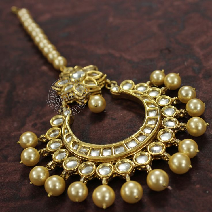 Gold Plated Maang Tikka studded with Simulated Kundan and Shell Pearl.Traditional wedding Jewelry. High quality finish with very shiny Gold Finish very similar Gold Jewlery.Tikka measures : Length (approx) -8