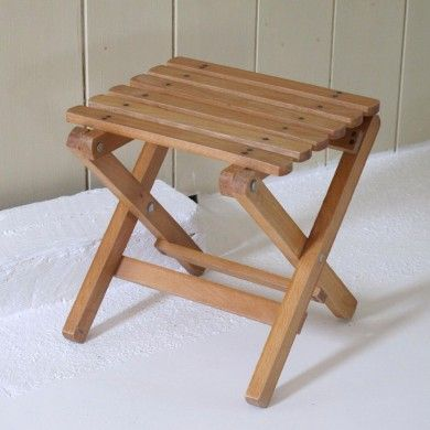 a small vintage wooden folding stool