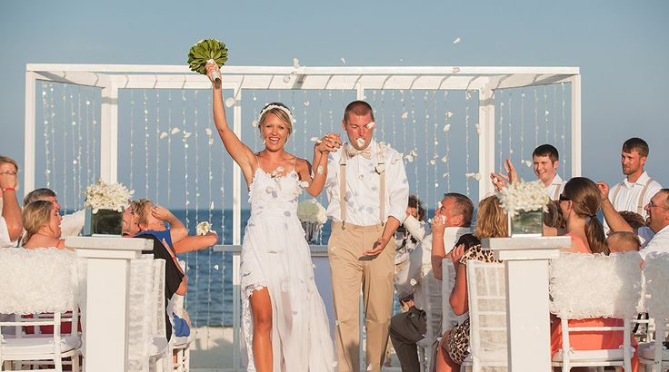 Guests celebrate the wedding and throw flower petals as bride and groom exit down the aisle   Palace Resorts Weddings ®