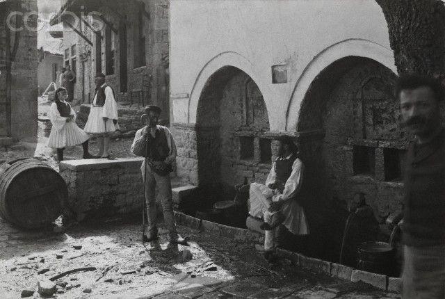 Men gather at the village fountains-Fred Boissonnas