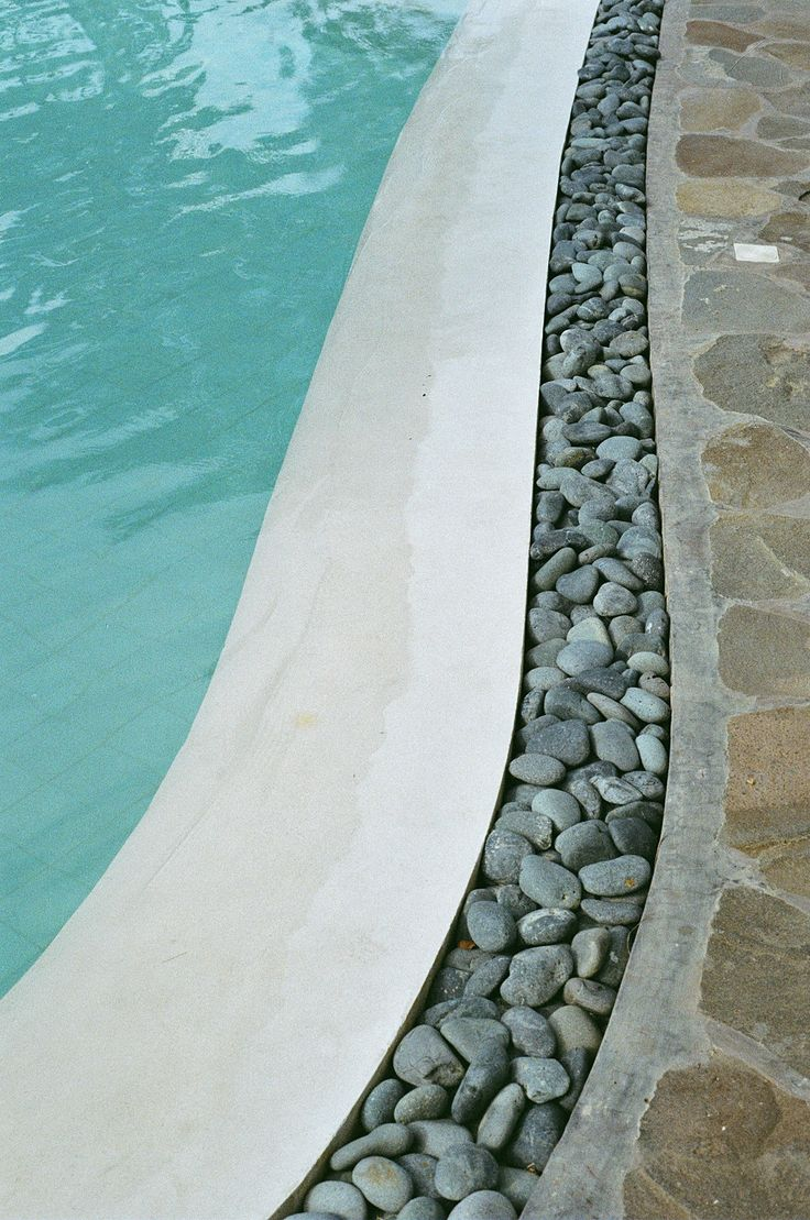 A good example of a poorly implemented pool side -- sloped pool edge with loose river rock trench