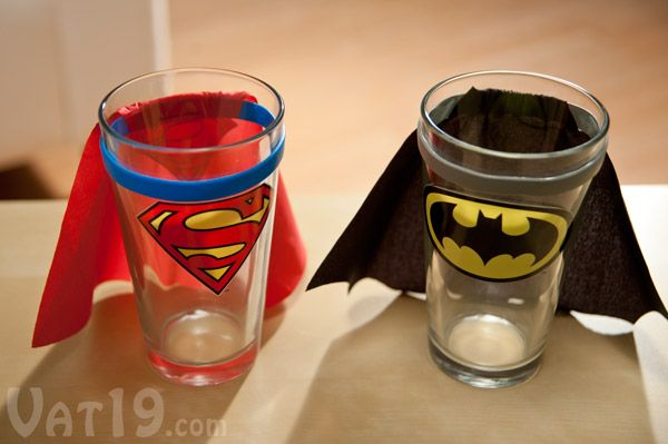 Superman and Batman Pint Glasses with capes sitting on a table.