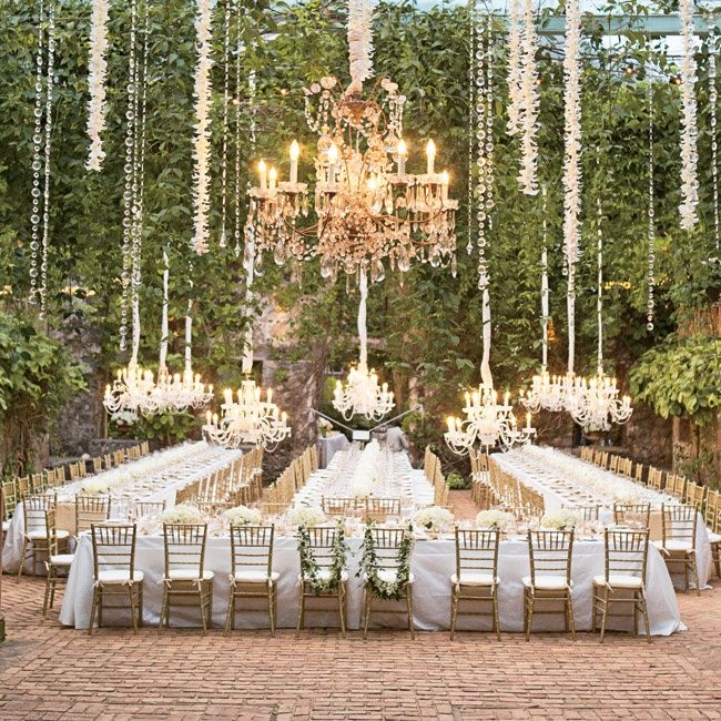 lush hanging vines, orchids and chandeliers mixed with white linens and gold chiavari chairs made for a sophisticated reception setting