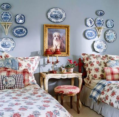 SFH adds: The arrangement of this blue plate collection with the sconce in the center is eye pleasing. I think the bed linens take away from this room, but love the furniture placement. I have fallen in love with the versatility of twin beds. The touches of red here are lovely.