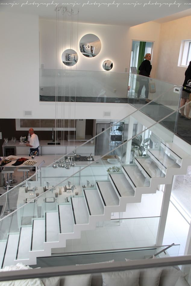 Modern white open plan living with glass balustrades and gorgeous lighting