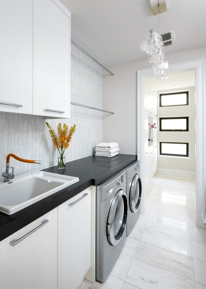 Bright laundry room, marble flooring, black countertops, pendants lighting, white cabinets | Barroso Homes