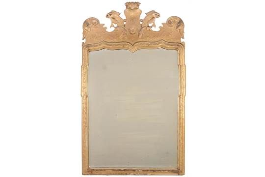 Lot 22 - A George I giltwood and gesso wall mirror  , circa 1720, the shaped bevelled plate within a