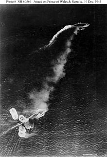 Japanese aerial photo of the initial attack on Prince of Wales (top) and Repulse. A short, thick plume of black smoke can be seen emanating from Repulse, which has just been hit by a bomb and surrounded by at least six near misses. Prince of Wales can be seen to be manoeuvring. The white smoke is from the funnels as the ships attempt to increase speed
