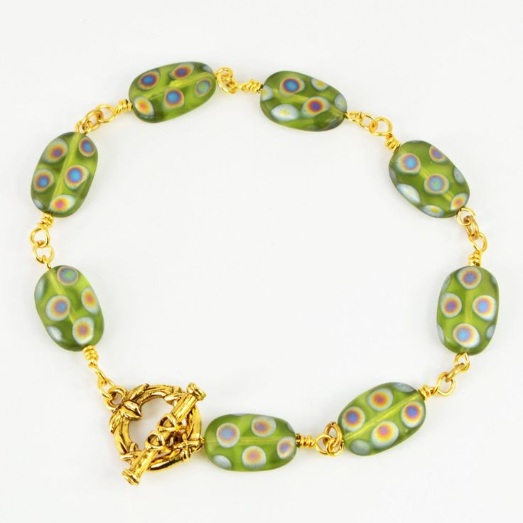 You'll be sure to capture attention in this elegant green Czech peacock glass link bracelet. Or give it to someone who loves beautiful things—like Mom. Each bead is wrapped by hand on gold-plated wire, and attached to a fancy gold tone bamboo toggle clasp. The bracelet is available in three lengths: 6.5, 7.5 or 8.5 inches. Please select your preference prior to checkout.  The Smallest Planet Guarantee  All Smallest Planet jewelry is handmade by me, Sara Kelly, in my home studio in San Die...