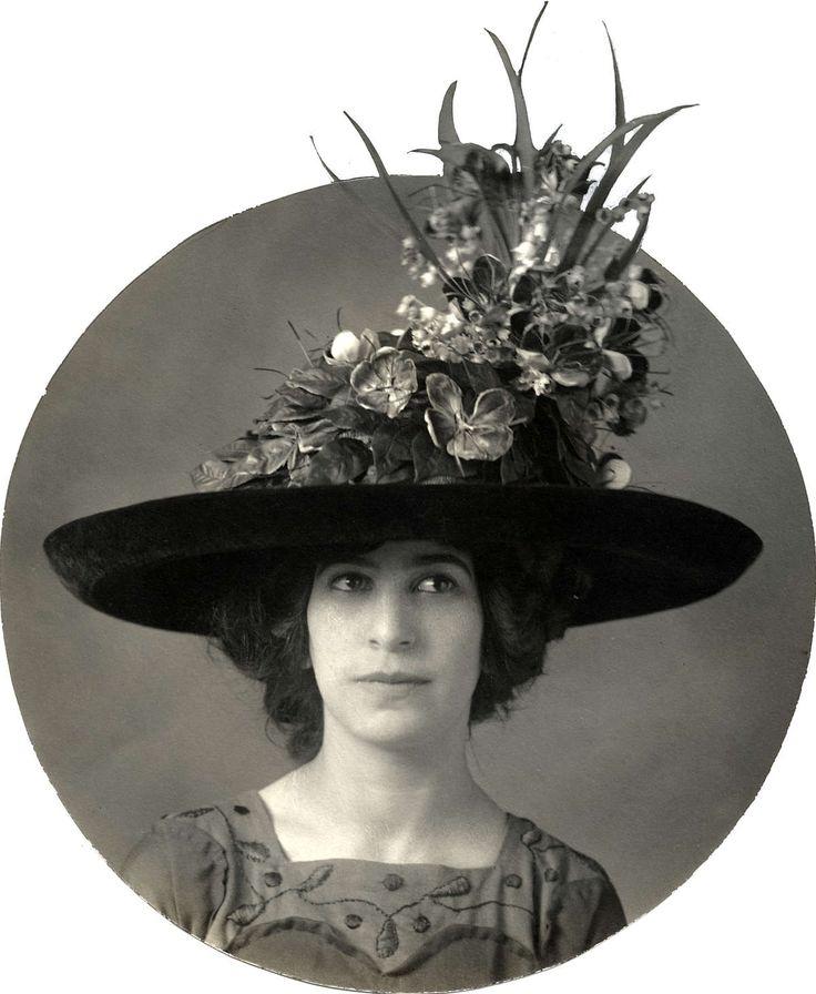 Damesmode vòòr 1914, hoeden. Nieuw model hoed van een grote firma in Amsterdam: wandelhoed van zwarte tagal-stro gegarneerd met modieuze veldbloemen. Nederland, 1912.