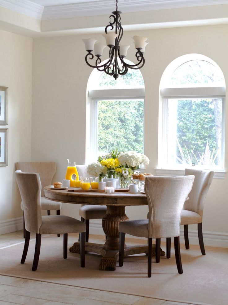 Food looks brighter and tastier in this white dining room with arched windows and an elegant chandelier. The sunny space is furnished with a reclaimed wood round table and chenille chairs.