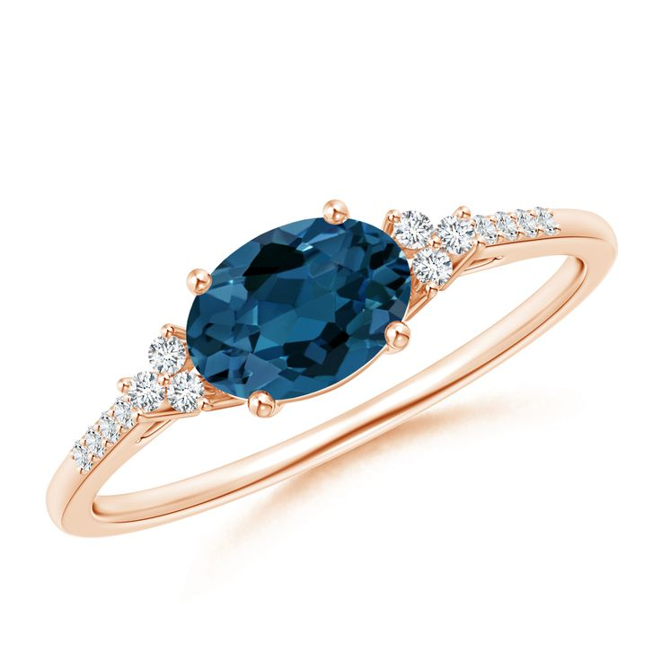 Glimmering trio diamonds illuminate the greenish blue gemstone while the additional diamond accents on the shoulders lend enhanced brilliance. Horizontally Set Oval London Blue Topaz Ring with Diamonds