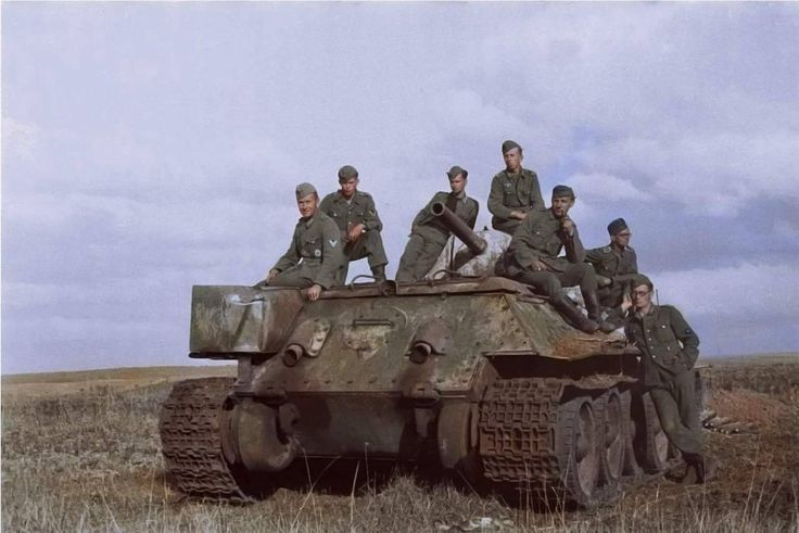 German troops on board an abandoned Soviet T34/76 tank, in a field in the Belgorod Region of Russia, about 40 kilometres north of the border with Ukraine. 1943. The Photographer, Franz Karl-Heinz...