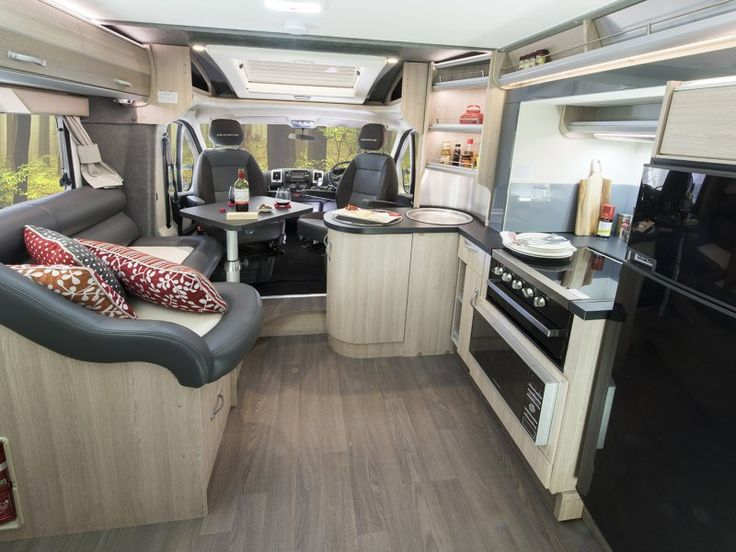 This is a view of the B7663SL Eyre motorhome standing in the middle of the motorhome looking toward the front of the vehicle. The slide out room is extended to open up the kitchen area and the cabin chairs swivel so they can be used with the living area when parked.