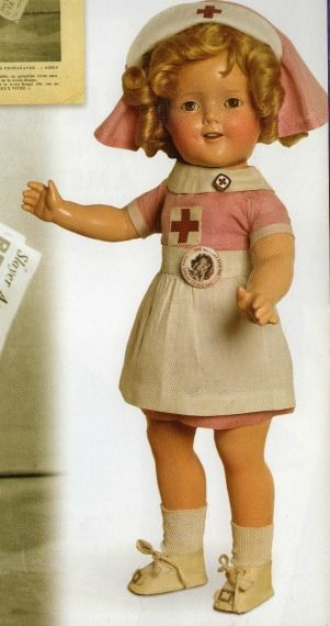 Composition Shirley Temple dressed in Red Cross nurse's outfit.