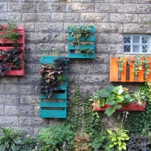 Wood Pallets painted bright and lined with burlap filled soil, & plants/ Beautiful, unique, and ecofriendly gardens.