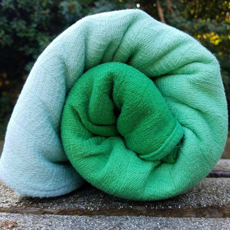 Dyed No 6- Mint Julep [Image of an emmeline textiles woven baby wrap- (partita number 6) rolled up on a park bench painted with white glitter in front of leafy green foliage. The wrap has a light emerald graduation dye saturated on one rail that gradually lightens to a pale mint on the opposite rail.] #emmelinetextiles #dyedno6 #babywrap #babywear #babywearing #graddyed #dyersofinstagram #ETCoterians #ETCoterie