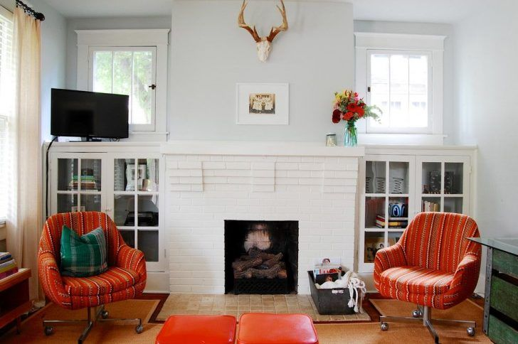 Horizon grey Benjamin Moore wall painting in vintage modern craftsman living room with built in storage cabinet glass doors and orange antique wheeled chairs