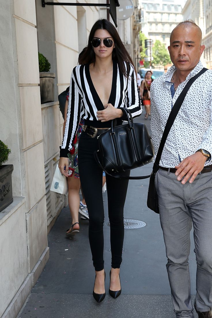 In Paris, she opts for a plunging striped top, high-waisted cigarette pants, a leather belt, and black pumps.   - MarieClaire.com