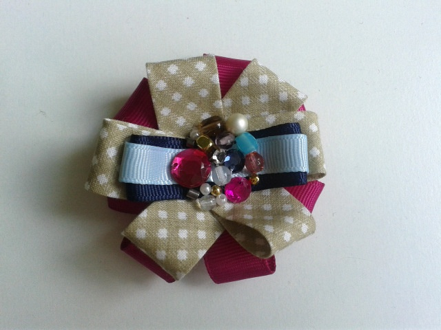 Brooch made of colored ribbons, beads and decorated with stones.
