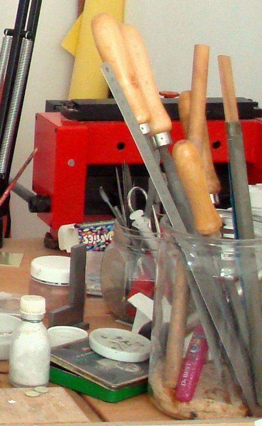 Im Bild vorne rechts seht ihr verschiedene große Feilen und Schmirgellatten zur Oberflächenbearbeitung. Die rote Maschine im Hintergrund dient zum Schneiden und Abkanten von Edelmetallblechen.