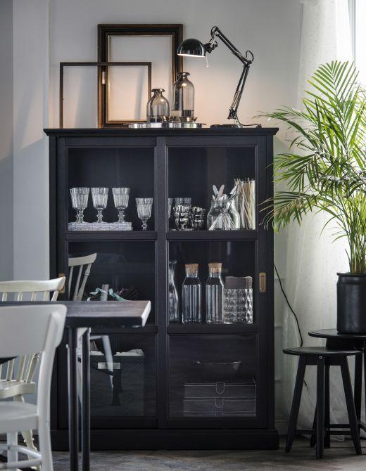 Ein Esszimmer mit MALSJÖ Vitrine schwarz lasiert, in der Gläser, Teller und Deko zu sehen sind. Eine Leuchte, Glasflaschen und leere Bilderrahmen stehen oben auf der Vitrine.