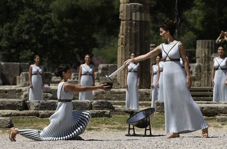 Image: Dancers dressed as priestesses hand over the Olympic flame during the ceremonial lighting of the Olympic flame in Ancient Olympia, Greece.