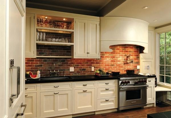 cream cabinets brick wall black counter in kitchen