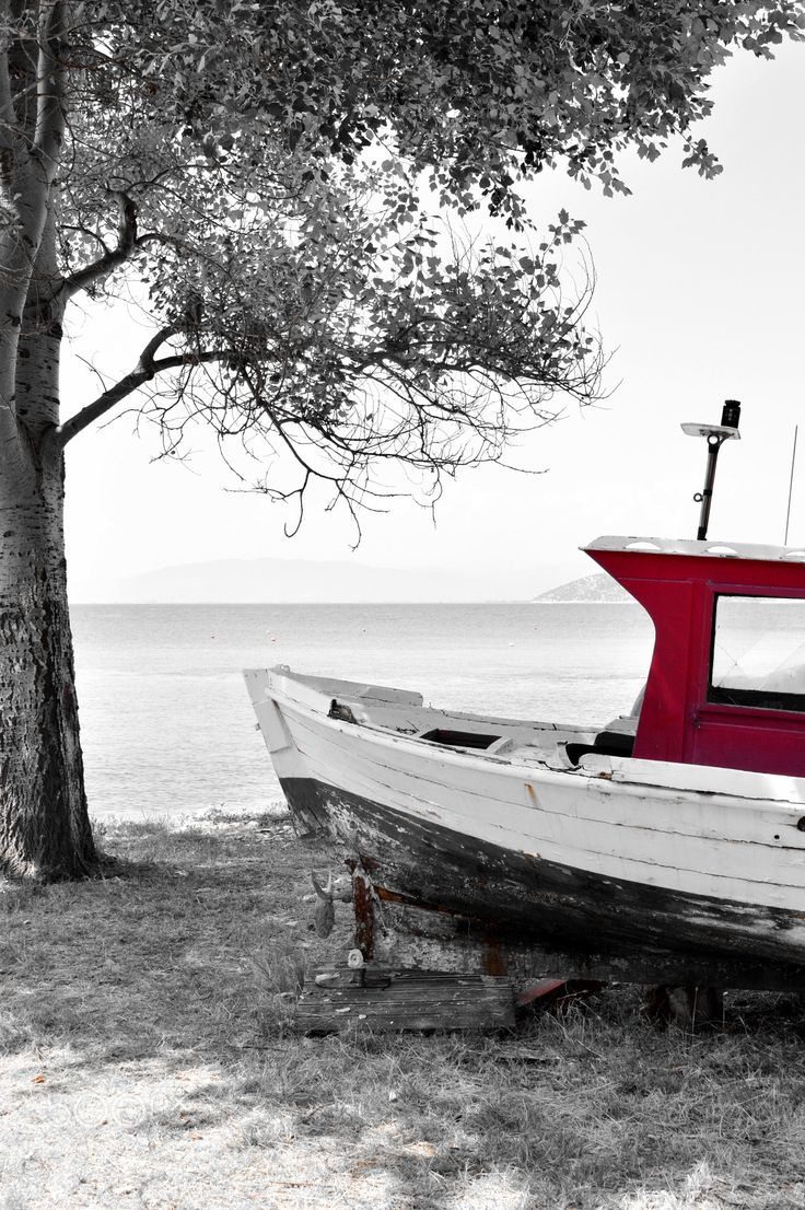 Red fishing boat - Black and white composition of a red fishing boat under a sea beside the sea.