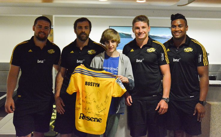"""Bostyn's one true wish is to go to the Gold Coast and visit all the theme parks! When Bostyn and his family arrived at the airport, we had a little surprise for him… His favourite rugby player Beauden Barrett was there to check his bags and passport in at the airport! Along with his friends Conrad Smith, Julian Savea and Dane Coles. Hurricanes manager Tony Ward said his players were """"only too happy to make someone's day and be part of Make-A-Wish"""". How awesome is that!"""