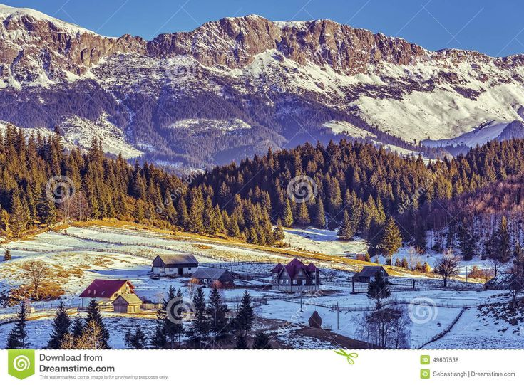 Sunny winter alpine scenery with small Romanian village in the valley of Bucegi massif, Fundata village, Brasov county, Romania.