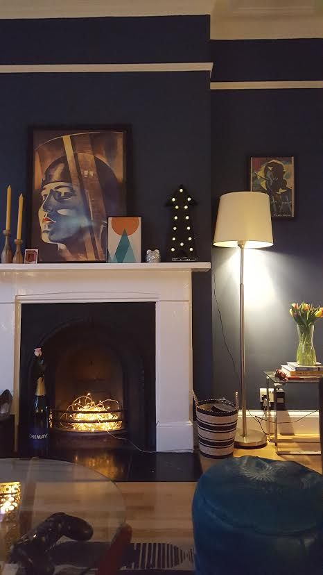 Living room by night. Dulux Breton Blue walls, Metropolis framed poster, Moroccan pouffe.