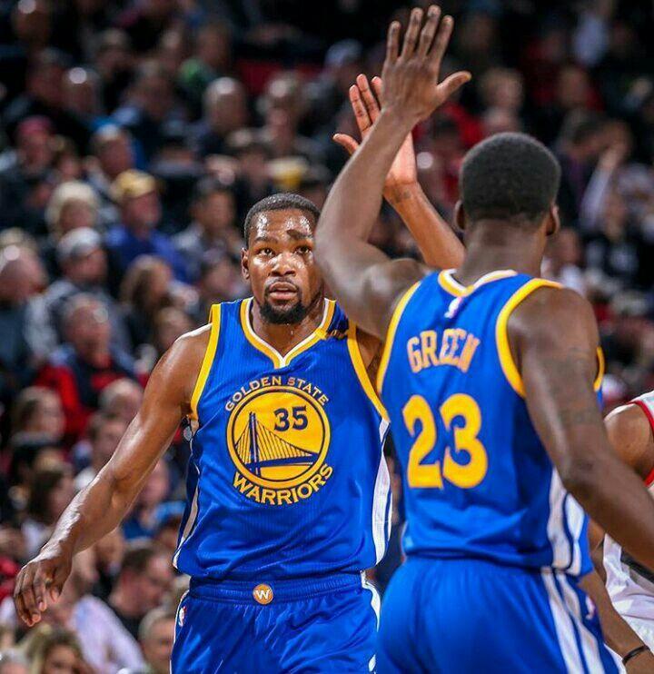 Kevin Durant high fives teammate Draymond Green