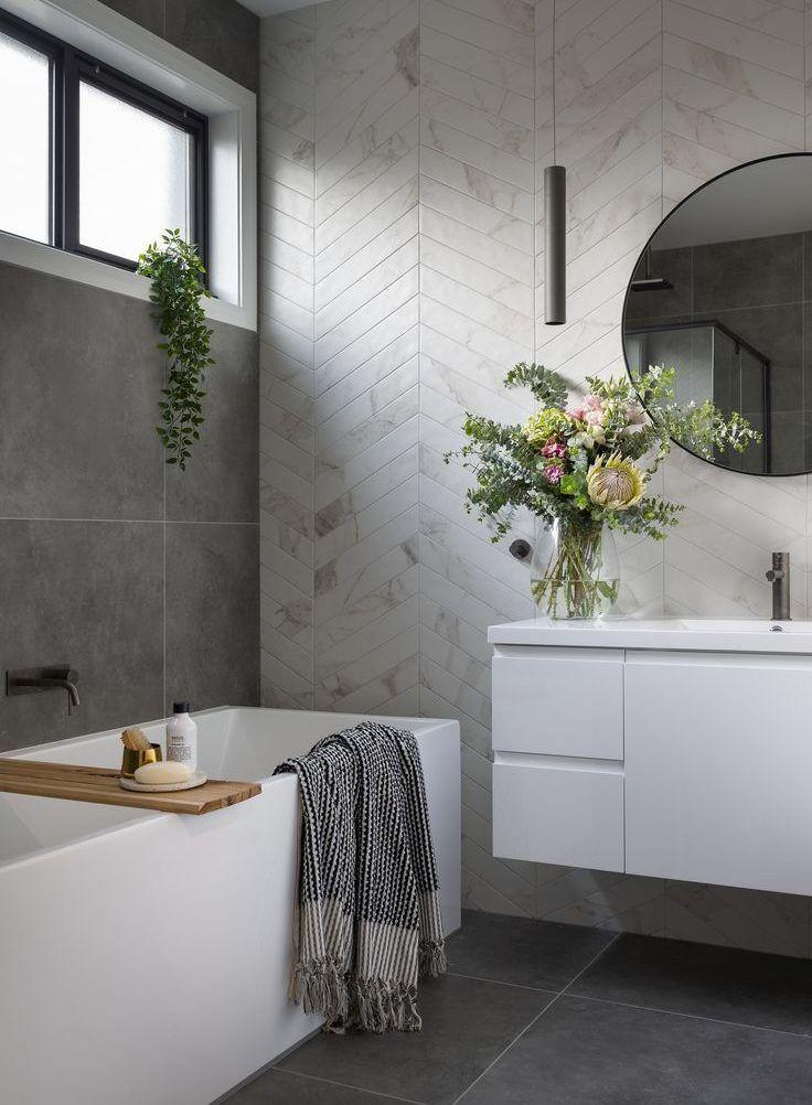 Ein modernes Bad mit Chevron Fliesen in Marmoroptik und Betonböden. Runden…   Bathroom interior ...