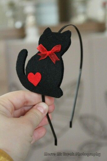 Diadema con gato negro y lazo rojo.