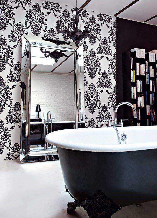 salle de bain noire et blanche avec baignoire ancienne en fonte à pattes de lion, papier peint imprimés baroques