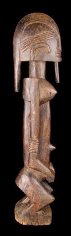 Dogon Maestro de Ogol féminine représentée debout, genoux pliés, bras le long du corps, mains de part et d'autre du nombril. Visage aux traits schématiques dont la coiffure est constituée d'une longue mèche centrale. Figuration d'un labret au niveau de la lèvre inférieure. Usage Habituellement gardée dans la maison du Hogon. Est placée sur la terrasse de la maison mortuaire, habillée, pour les funérailles. Familles riches seulement.
