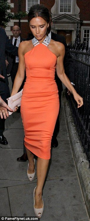 Tangerine dream: Victoria Beckham  arriving at a party in London wearing one of her own designs.