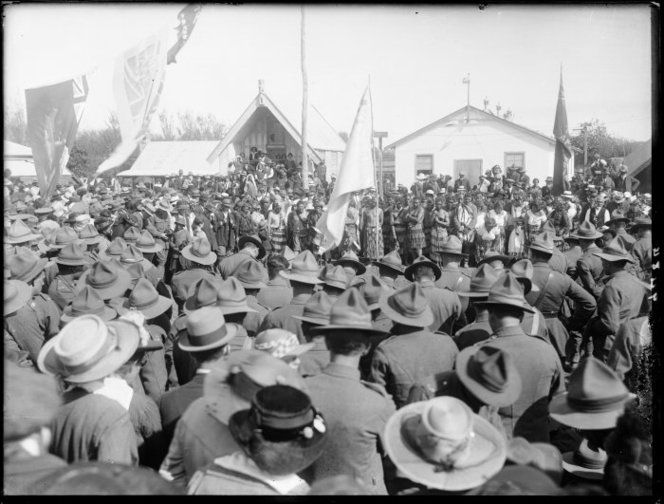 Return of the Pioneer (Maori) Battalion to Putiki Pa, Wanganui district, New Zealand, after World War 1. Shows uniformed soldiers and the welcoming party. The Moutoa flag is in the centre. Other flags unidentfied. Photograph taken by Frank J Denton in 1918.
