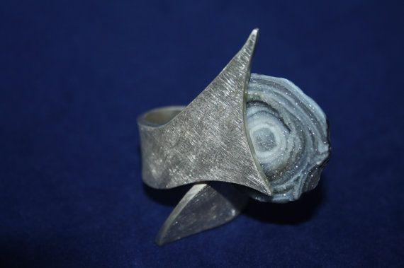 Dies ist mein persönlicher Ring (d.h. es ist ein Musterring).  Dieser Ring aus massivem 2 mm starken 935er Silber ist sandmatt glitzernd vollendet, in einer Haiflosse auslaufend geschmiedet und mit einem wundervollen grauen riffähnlichen Edelstein versehen.  Dieser Ring ist mit anderen Edelsteinen und in anderen Materialstärken und -strukturen umsetzbar. Grundsätzlich sind die Werke der Design-Kollektion aber einzigartig und sollen Euch inspirieren. Preise der Schmuckstücke sind immer…