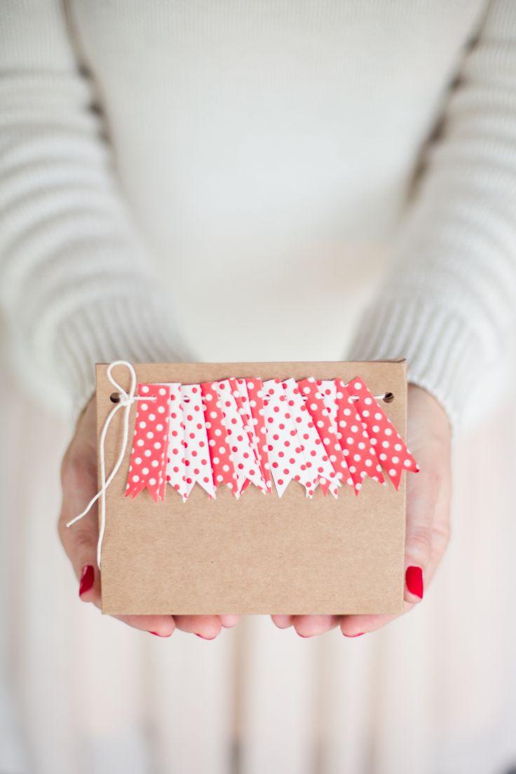 Pacchetto regalo creativo decorato con una frangetta di bandierine di carta a pois bianchi e rossi